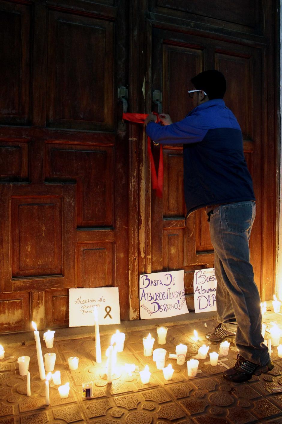 Los vecinos colocaron cintas de color rojo, velas y carteles frente a la puerta de la iglesia para pedir la renuncia del sacerdote. (Foto: Gustavo Rodas/Nuestro Diario)