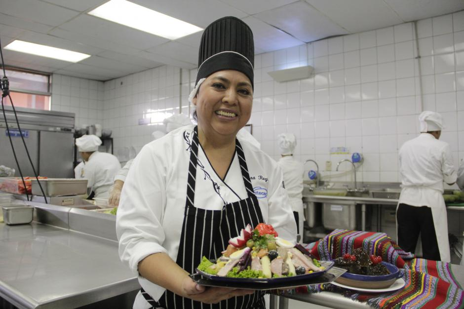 La chef Aura Marina Equité muestra uno de los platillos preparados por los alumnos del Intecap. Los estudiantes se preparan para la venta anual de fiambre de este 30 de octubre. (Foto: Fredy Hernández/Soy502)