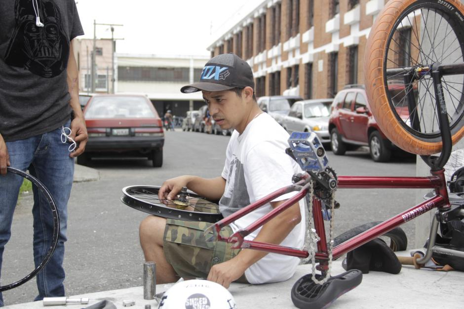 Los bikers le dan mantenimiento a sus bicicletas antes de empezar a hacer sus piruetas. (Foto: Fredy Hernández/Soy502)
