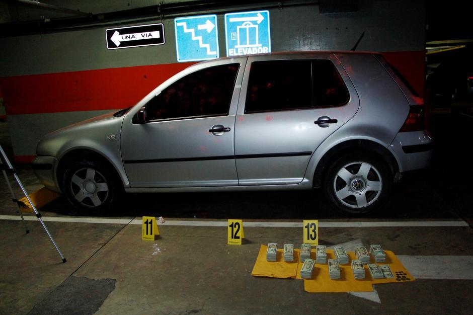 Vista del auto y el dinero encontrado en el sótano del hotel de la zona 10. (Foto: PNC)
