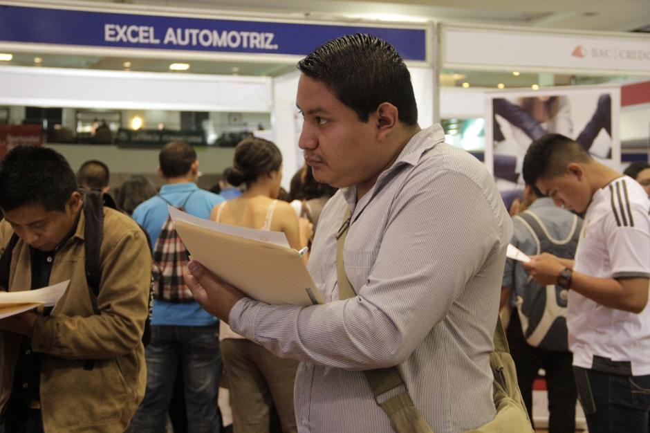 Los asistentes llenan los formularios de las empresas donde podrían encontrar un nuevo ambiente. (Foto: Fredy Hernández/Soy502)