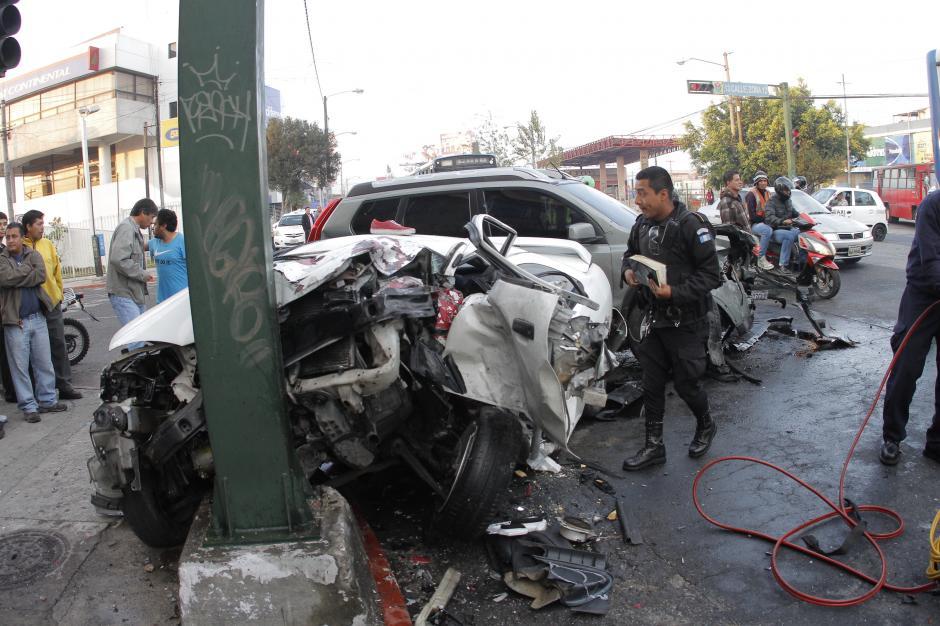 El agente de la PNC se acerca al vehículo colisionado para observar qué hay adentro. (Foto: René Ruano/Nuestro Diario)