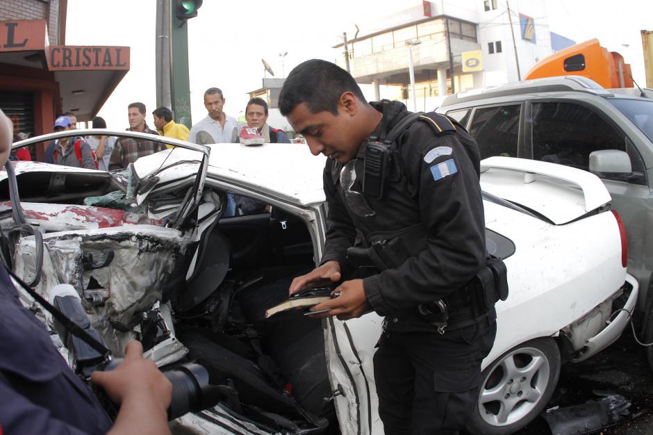 Antes de sacar del carro el maletín negro de la computadora, toma los documentos de la persona accidentada. (Foto: René Ruano/Nuestro Diario)