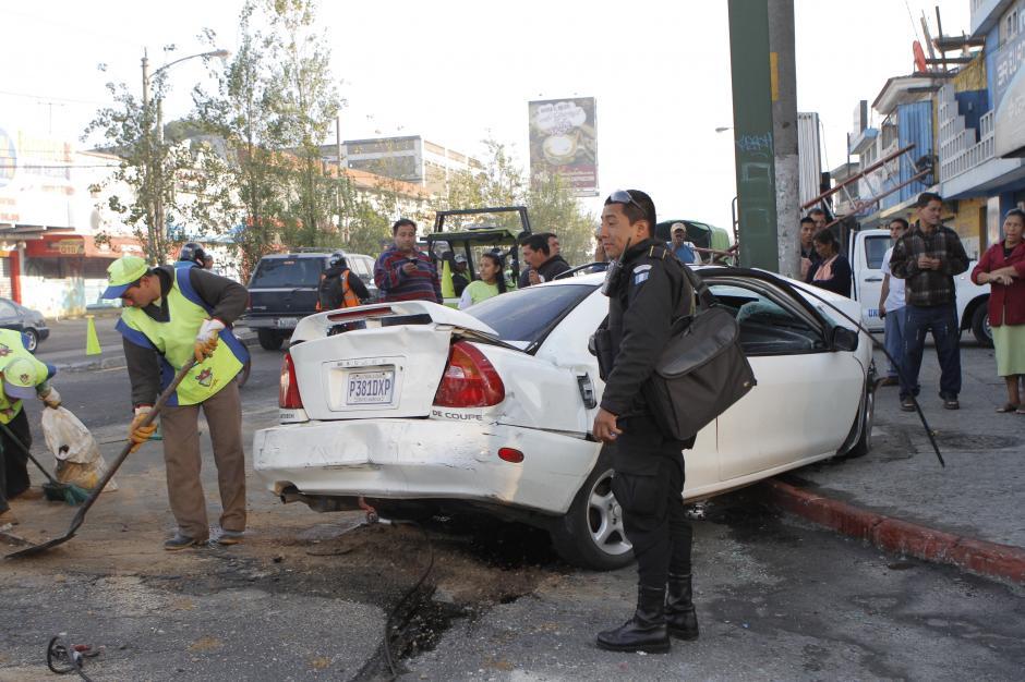 Minutos después el agente de la PNC aparece con un maletín tomado del vehículo.(Foto: René Ruano/Nuestro Diario)
