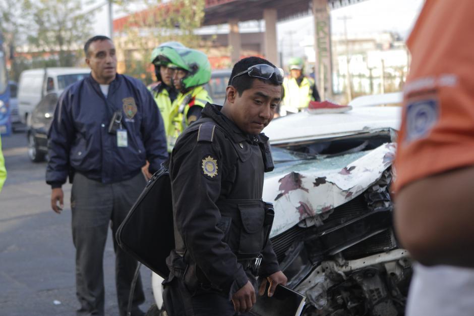 Observe al agente cargar cuidadosamente el maletín decomisado, luego de que dos vehículos colisionaran en la Avenida Petapa. (Foto: René Ruano/Nuestro Diario)