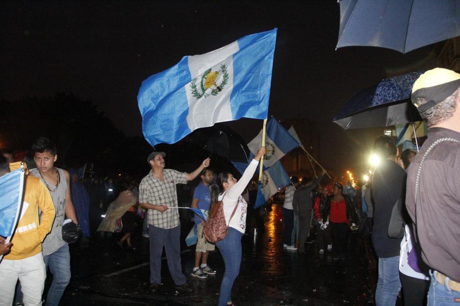 Algunos ciudadanos llegaron con banderas frente al Palacio Nacional de la Cultura tras su jornada laboral.(Foto: Fredy Hernández/Soy502)