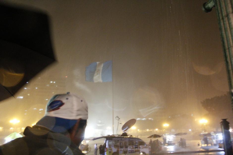 El pabellón nacional ondeó y se extendió en su totalidad durante la lluvia acompañada de fuertes vientos. La tormenta provocó apagones en el lugar, pero no ahuyentó a la gente.(Foto: Fredy Hernández/Soy502)