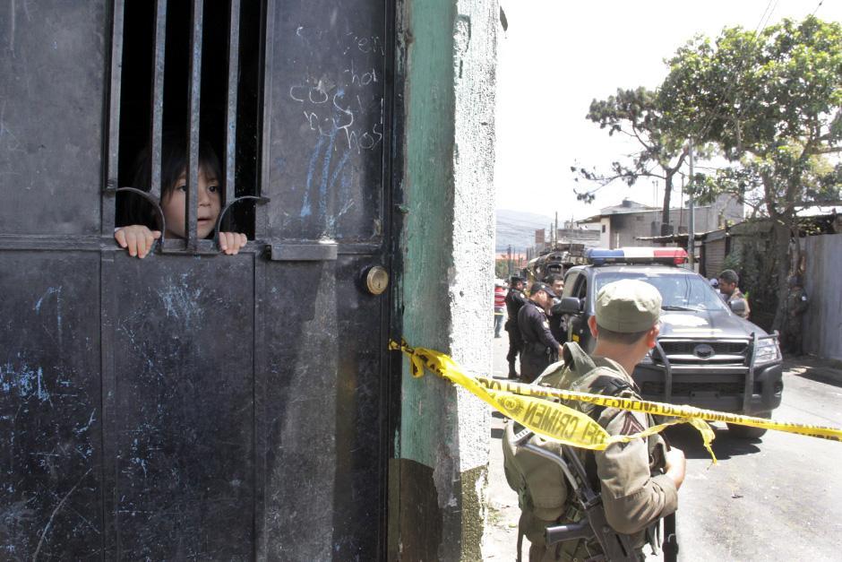 Una niña observa la escena del crimen tras el ataque (Foto: David Ixbalán/Soy502)