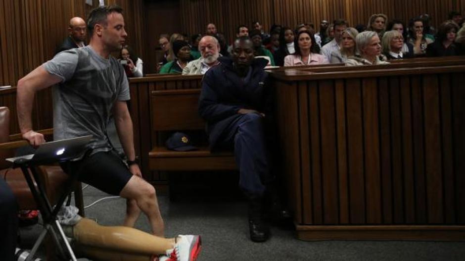 Oscar Pistorius se levanta ante el juzgado que lo acusa del asesinato de su prometida Reeva Steenkamp. (Foto: AFP)