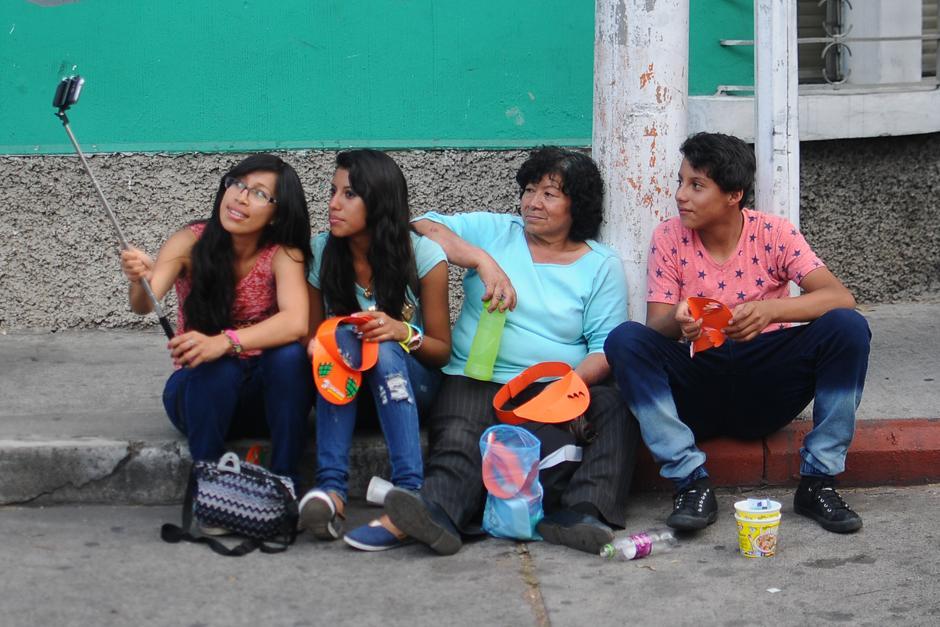 """Mientras esperan el paso procesional, aprovechan para hacer """"selfies""""  (Alejandro Balán / Soy502)"""