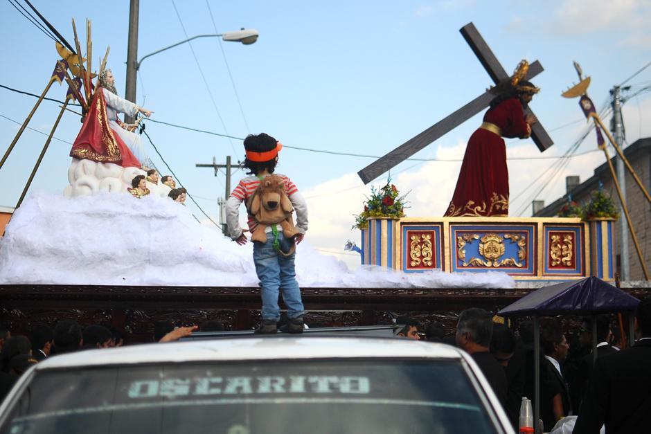Un niño observa desde el techo de un vehículo el paso de la procesión.  (Alejandro Balán / Soy502)