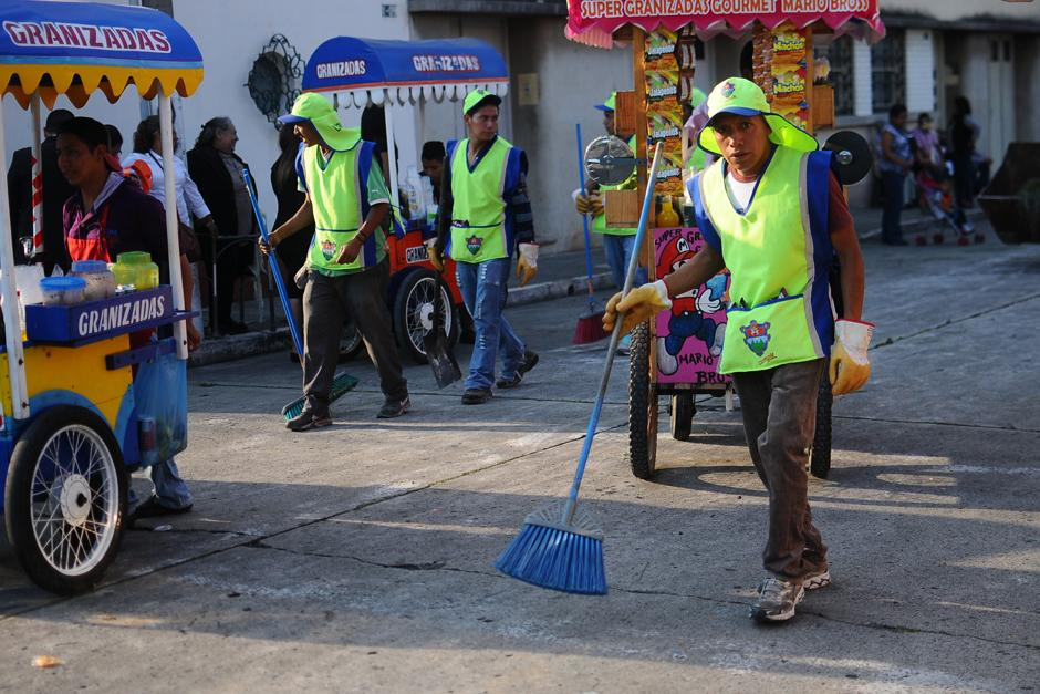 Inmediatamente atrás de las andas, personal de la municipalidad limpia los restos de las alfombras. (Alejandro Balán / Soy502)