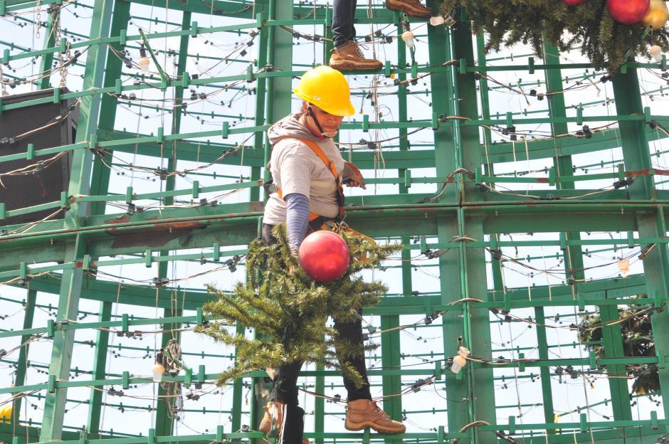 Una cantidad considerable de mujeres forma parte de los trabajadores que escalan grandes alturas para la colocación de ramas en la estructura del árbol(Foto: Alejandro Balán/Soy502)