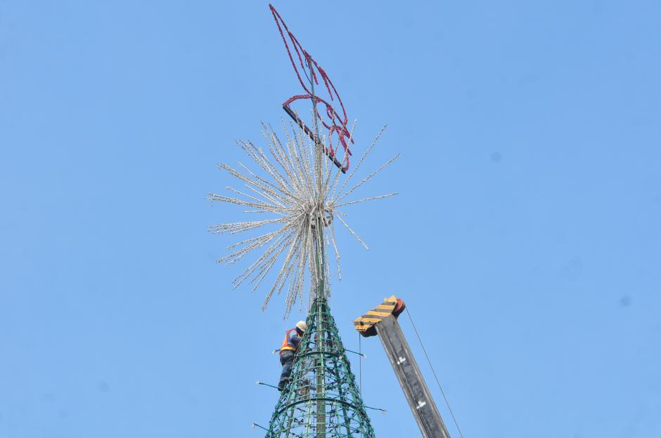 Un hombre en la cima del árbol esta a cargo de la instalación de las partes que forman la estrella (Foto: Alejandro Balán/Soy502)