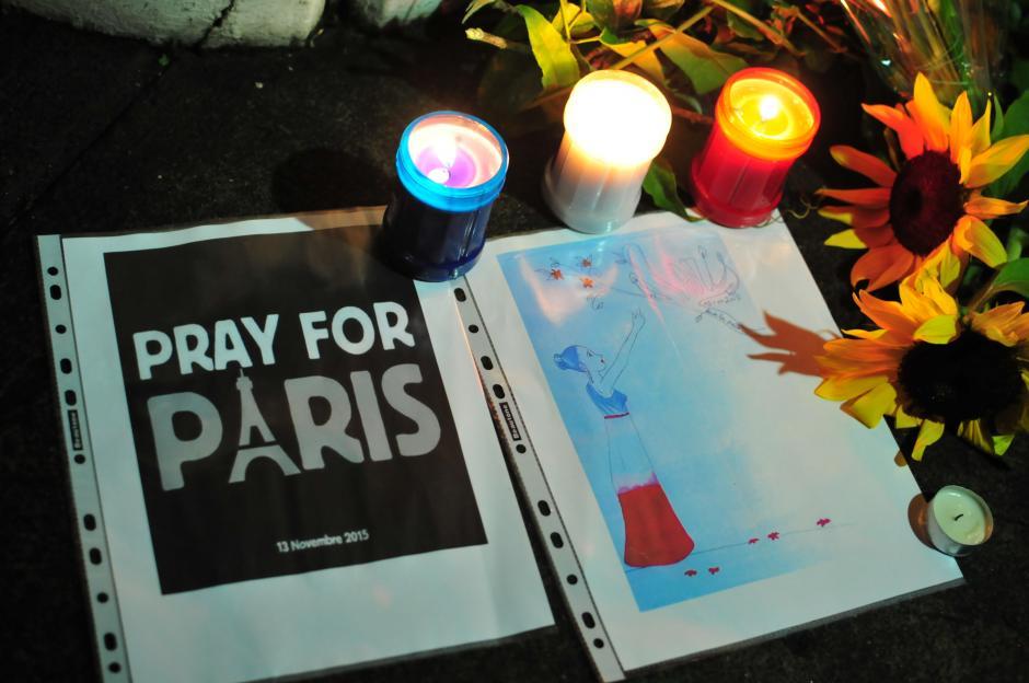 """Uno de los asistentes acompañó las flores y velas con esta impresión de """"Reza por París"""" (Foto: Alejandro Balan/Soy502)"""