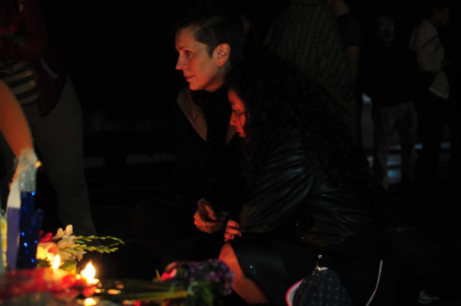 Valerie Julliand (al fondo), Coordinadora Residente del Sistema de Naciones Unidas en Guatemala, al momento de dejar una vela al pie de la bandera de Francia. (Foto: Alejandro Balan/Soy502)