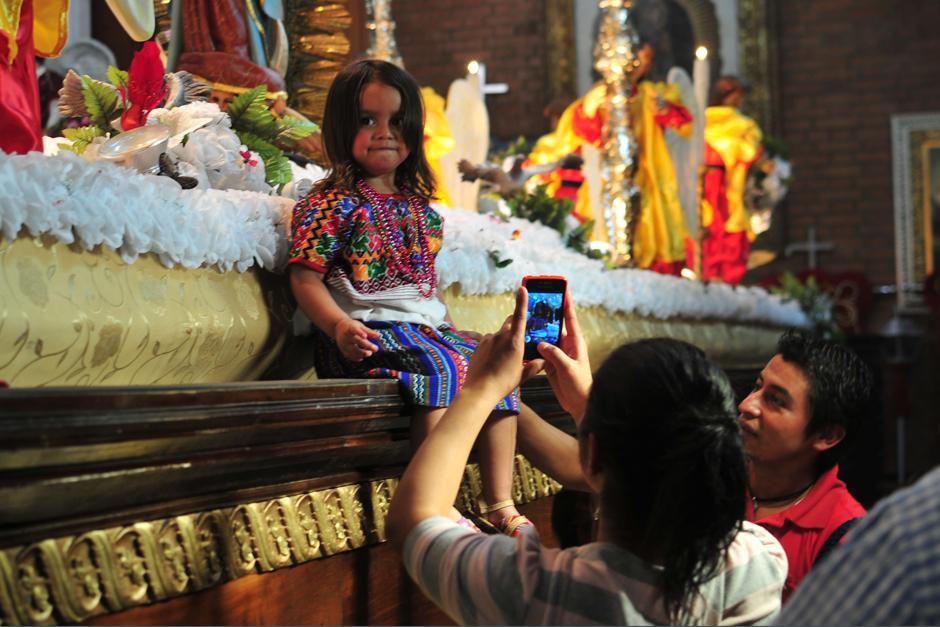 Los padres visitan a la Virgen acompañados por los pequeños que visten accesorios típicos. (Foto: Alejandro Balán/Soy502)