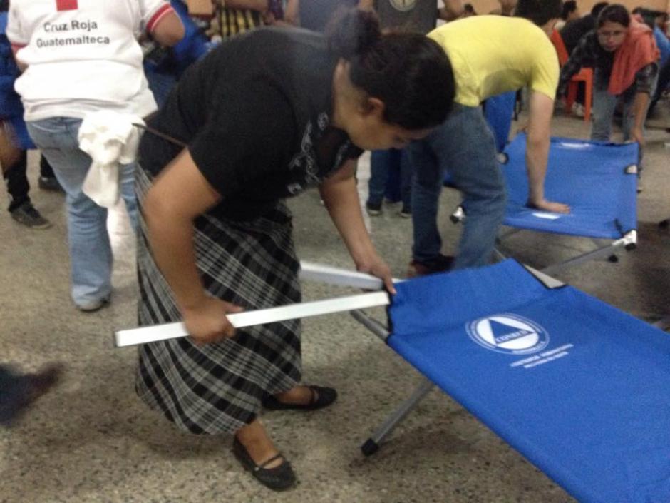 Las mujeres preparan las camas provisionales para pasar esta noche. (Foto: Fredy Hernández/Soy502)