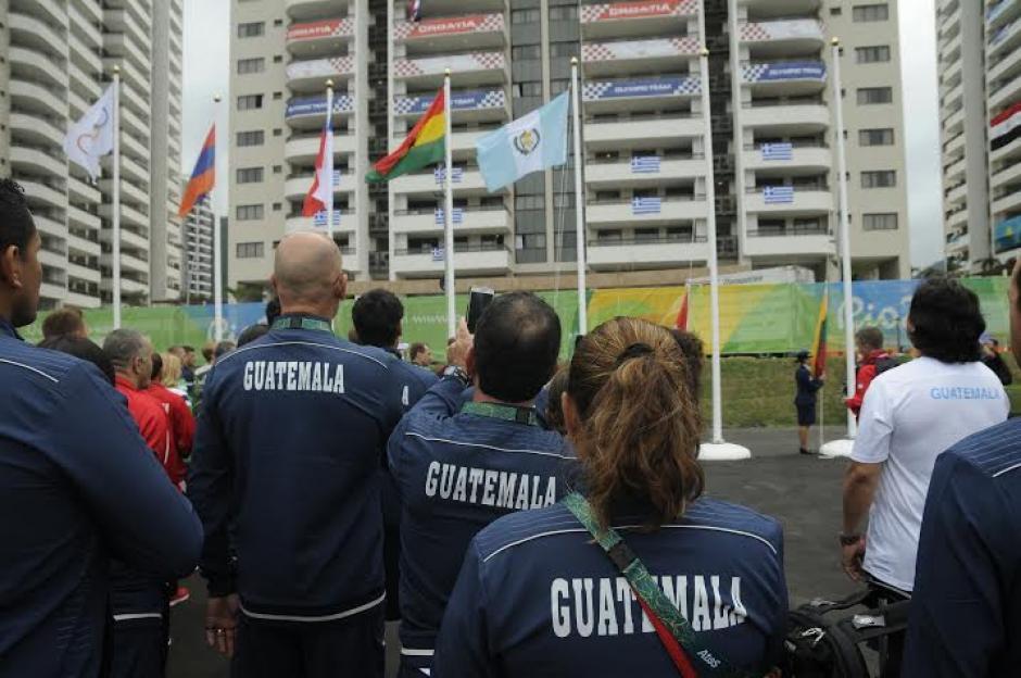 Delegados guatemaltecos, entre atletas y dirigentes, ven la bandera de Guatemala ondear en Río de Janeiro. (Foto: Aldo Martínez/Nuestro Diario)