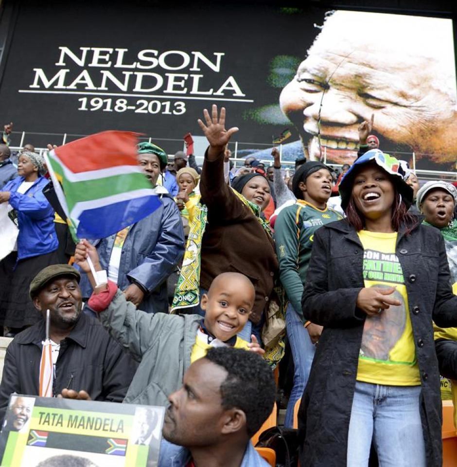 Varios asistentes animan durante el servicio religioso oficial en memoria del fallecido expresidente sudafricano Nelson Mandela, en el estadio FNB de Soweto, Johannesburgo, Sudáfrica, el 10 de diciembre del 2013. (Foto: EFE)