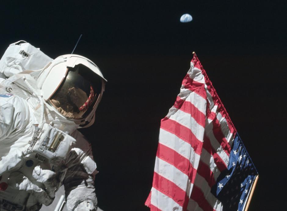 El piloto del módulo lunar del Apolo 17, Harrison Schmitt, posa con la bandera estadounidense, con la tierra de fondo en diciembre de 1972. (Foto: Nasa)