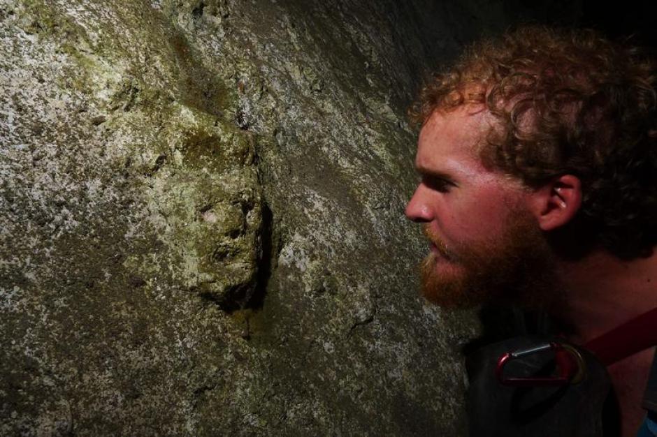 El arqueólogo Greg Schwab observando una cara grabada en una cueva de la región de los Nueve Cerros.