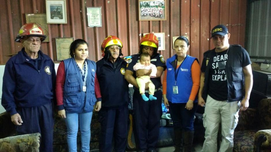 La bebé Angely de León Sosa es cargada en brazos por un oficial de bomberos Municipales mientras se documenta la recuperación. (Foto: PDH)