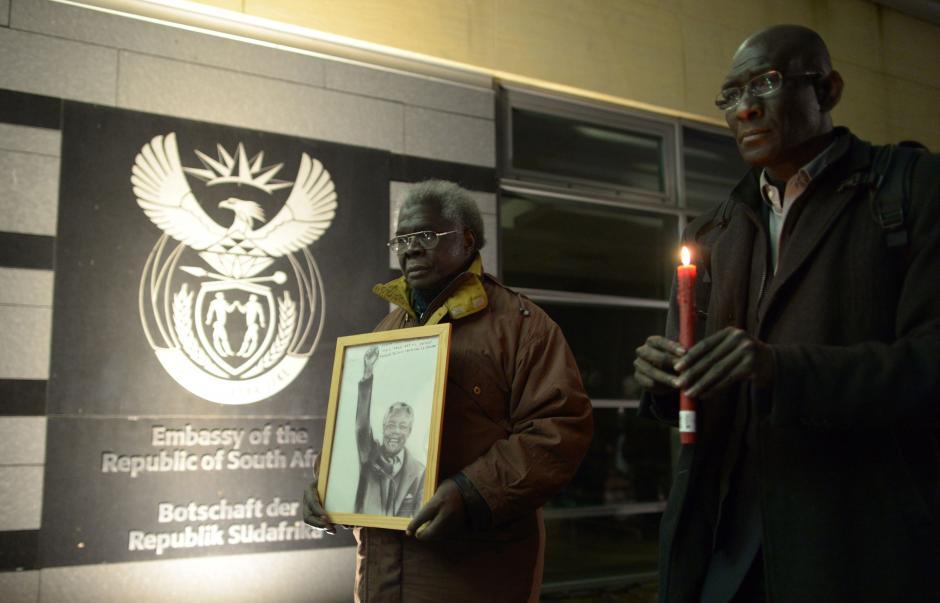 Un hombre sostiene un retrato del expresidente sudafricano Nelson Mandela en las afueras de la embajada sudafricana en Berlín. (Foto:AFP)
