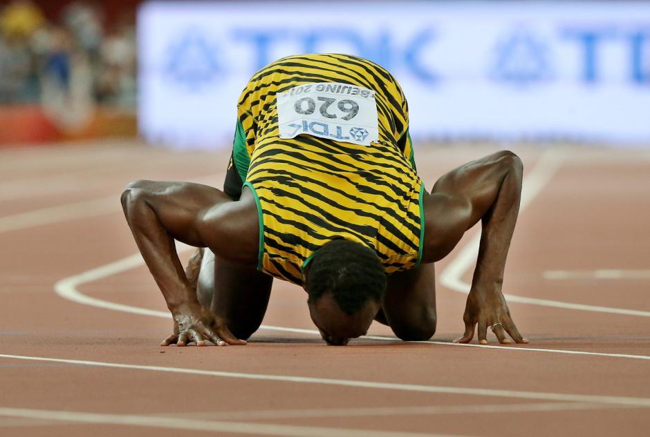 El jamaiquino Usain Bolt besa el suelo luego de ganar la final de los 200 metros durante los Juegos Mundiales de Atletismo. (Foto: Srdjan Suk/EPA)
