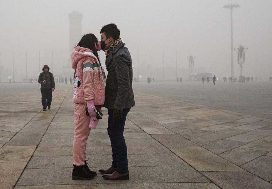 El beso de esta pareja se dio durante el día con más polución en la ciudad de Pekín, China. (Foto: Kevin Frayer/Getty Images)