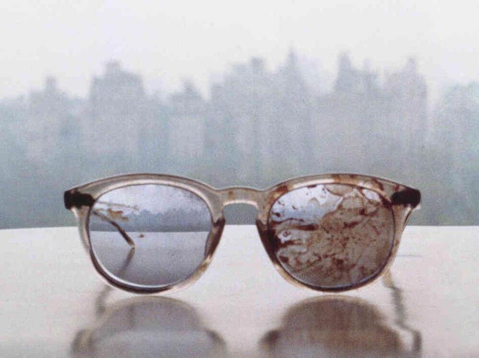 Los anteojos que llevaba John Lennon el día de su asesinato, fotografiados por su novia Yoko Ono, con la ciudad de Nueva York de fondo.