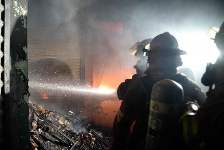 Bomberos luchan por sofocar el fuego en el interior del Mercado La Terminal. (Foto: Esteban Biba/ Soy502)