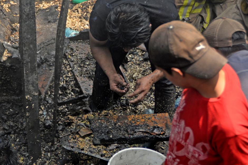Un vendedor busca fichas entre los escombros. (Foto: Esteban Biba/Soy502)