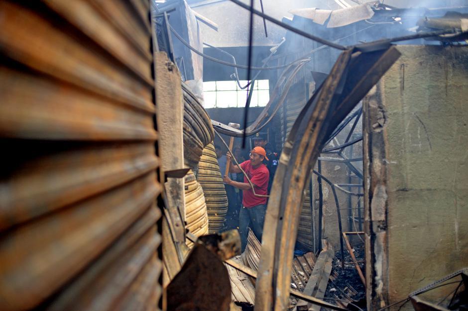 Vendedores rompen las persianas de sus locales para buscar restos de su mercadería. (Foto: Esteban Biba/Soy502)