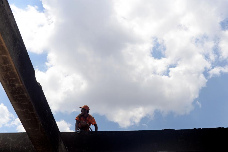 Los trabajadores desprenden las láminas del techo para que no caigan de imprevisto. (Foto: Esteban Biba/Soy502)