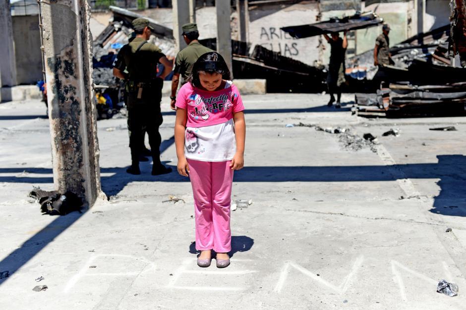 Una estudiante ve el texto trazado con piedra, que conserva el lugar donde antes funcionó el Programa Educativo del NIño y Niña, Adolescente Trabajador PENNAT. (Foto: Esteban Biba/Soy502)