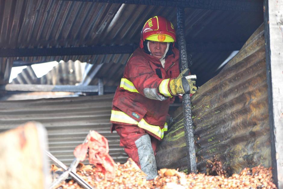 Los bomberos descombran para evitar que el fuego continúe.  (Foto: Jesús Alfonso/Soy502)