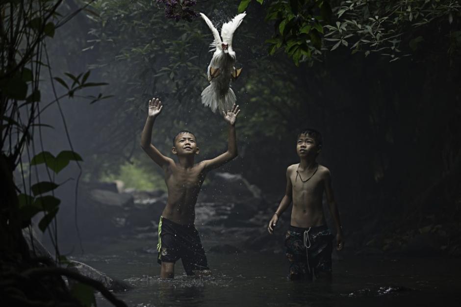Unos niños tratan de atrapar a un pato en un riachuelo cercano a una catarata en la provincia Nong Khai, Tailandia. (Foto: Sarah Wouter/National Geographic)