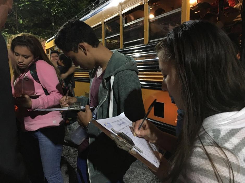 Los estudiantes deben anotarse en listados antes de subir a los buses.  (Foto: Fredy Hernández/Soy502)