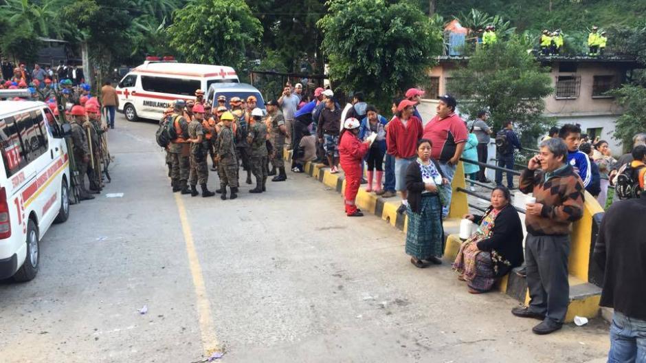Familiares de decenas de personas desaparecidas esperan en las afueras del área de la Colonia El Cambray II, en Santa Catarina Pinula. (Foto: Jorge López/Soy502)