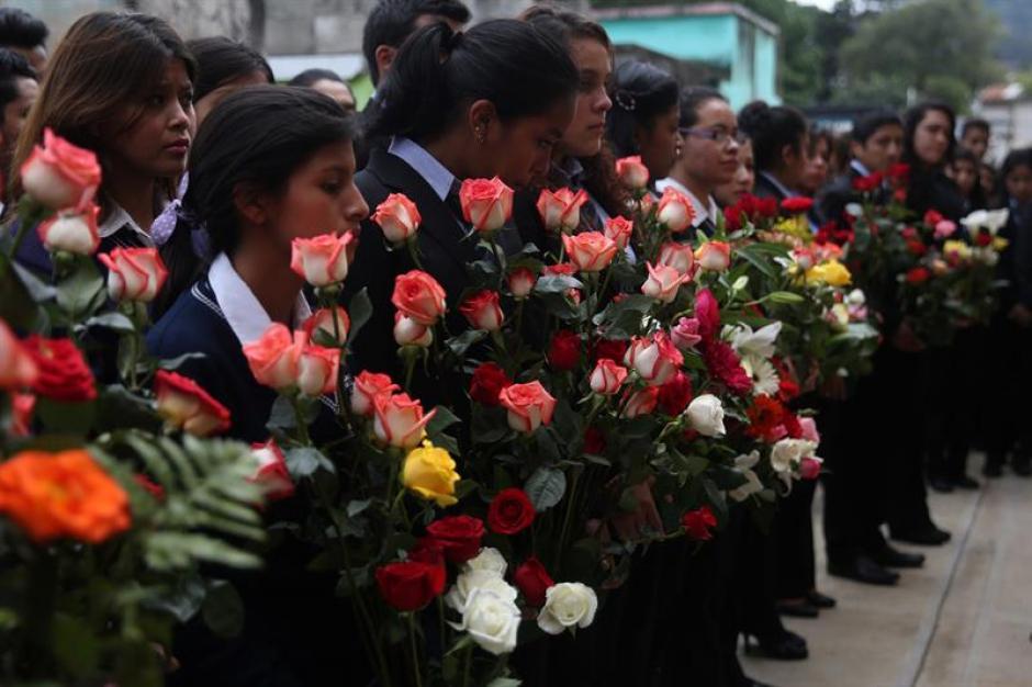 Los vecinos, familiares y amigos llevaron flores y rezaron frente a las tumbas.  (Foto: EFE)