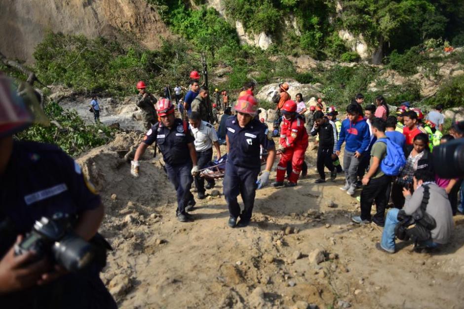 Los bomberos extraen a uno de los fallecidos por el derrumbe en El Cambray II en Santa Catarina Pinula. (Foto: Jesús Alfonso/Soy502)