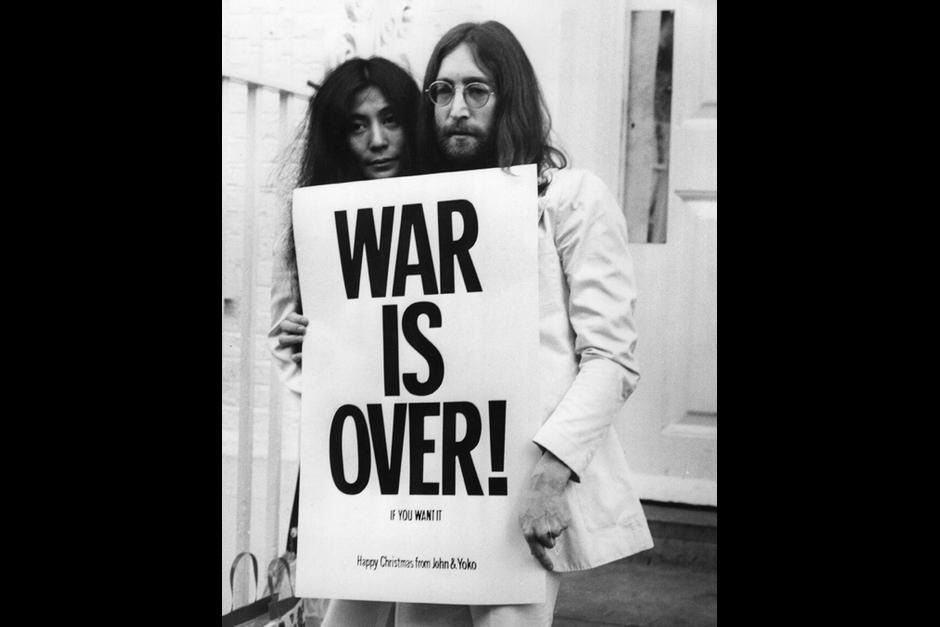 Lennon y su esposa muestran un cartel con la leyenda: Se terminó la guerra.