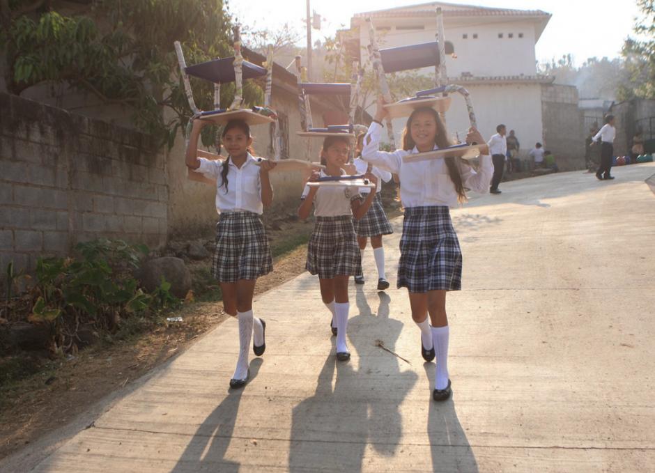 Los alumnos de la escuela cargaron los pupitres donados. (Foto: Gobierno)