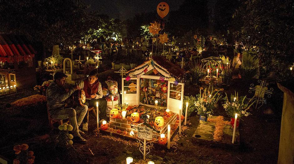 En la Ciudad de México, jovenes se sientan al lado de las tumbas. (Foto: elcomercio.pe)