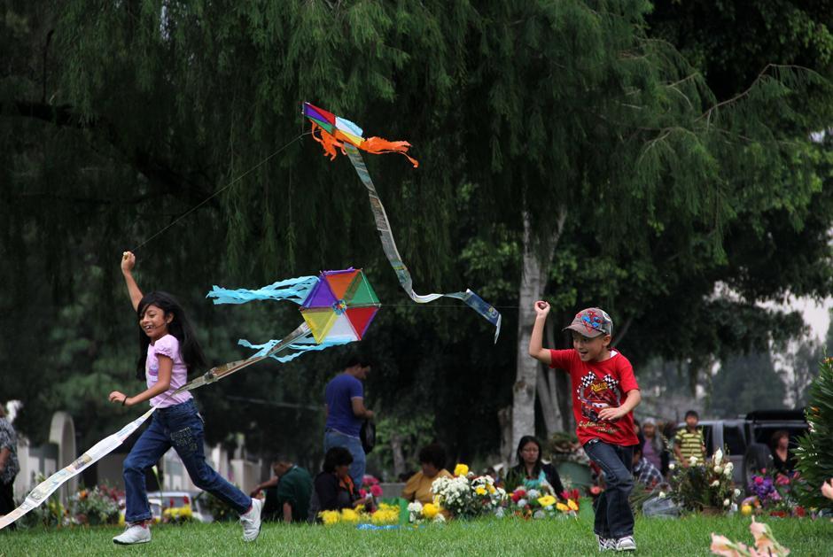 Los cementerios son el uno de noviembre el punto de encuentro entre vivos y muertos. Mientras tanto los más pequeños disfrutan del momento que les puede brindar un amplio espacio verde y el ánimo de volar un barrilete. Foto: Luis Barrios