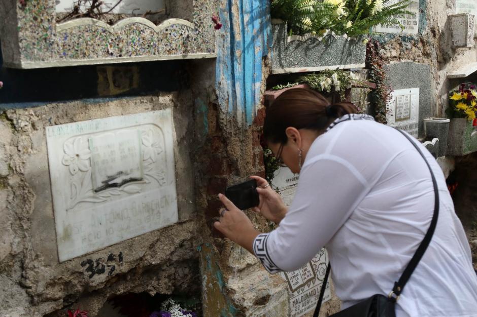 Veronica Barberena fotografía la lapida de su padre fallecido en 1979. (Foto: Alejandro Balán/ Soy502)