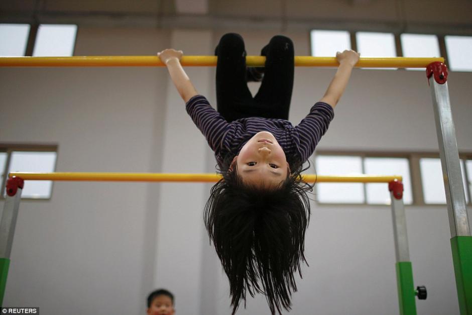 Una de las estudiantes práctica en las barras asimétricas. (Foto: dailymail.co.uk)