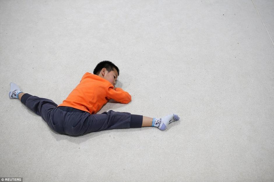 Durante el receso, este estudiante de gimnasia realiza un estiramiento de piernas. (Foto: dailymail.co.uk)