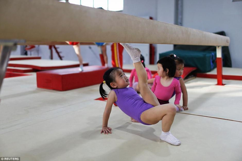 La niña extiende la pierna para llegar a una barra de equilibrio durante la clase de gimnasia. (Foto: dailymail.co.uk)